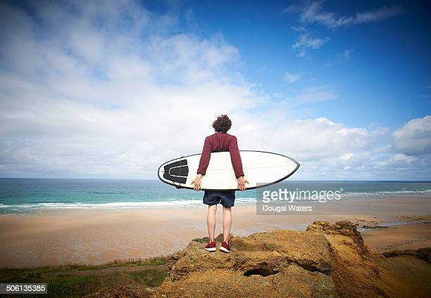 Man holding surfboard looking out toward sea
