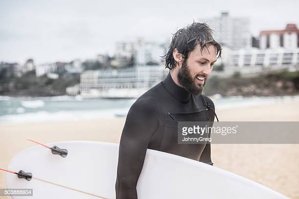 Man holding surfboard on beach looking down smiling