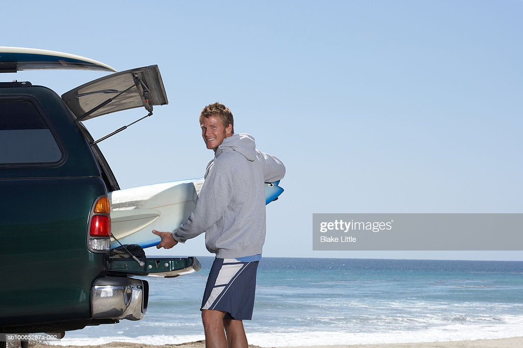 Man holding surfboard, smiling, portrait : Foto stock