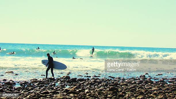 Man Holding Surfboard While Walking On Shore Against Sky