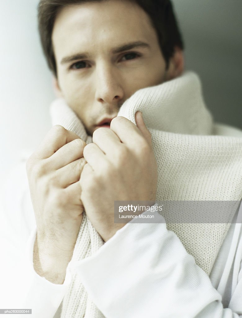 Man holding sweater around neck, covering part of face : Stockfoto