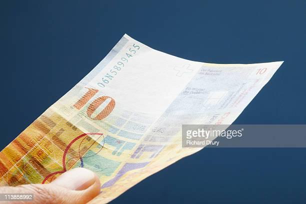 Man holding Swiss ten franc note