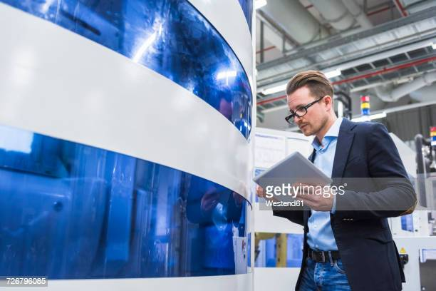 Man holding tablet looking at machine in factory shop floor