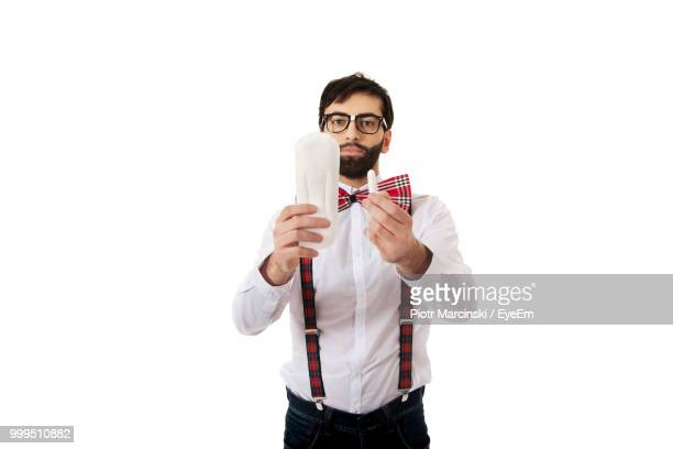 man holding tampon and padding while standing against white background - padding stock photos and pictures
