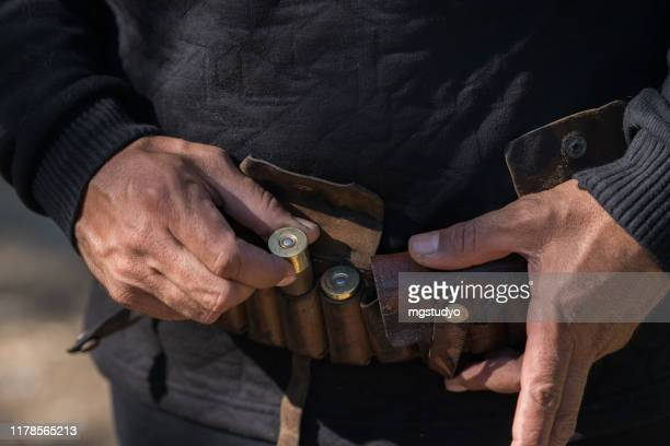 man holding tape with cartridges for hunting rifle - ammunition stock pictures, royalty-free photos & images