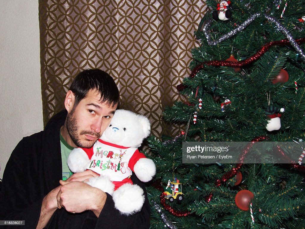 1867000a5a Man Holding Teddy Bear While Sitting By Christmas Tree Stock Photo ...