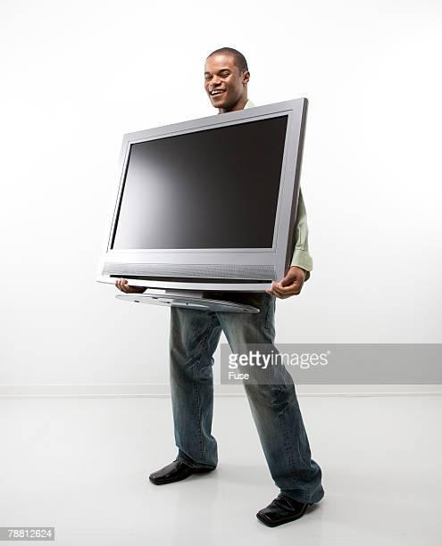 Man Holding Television Set