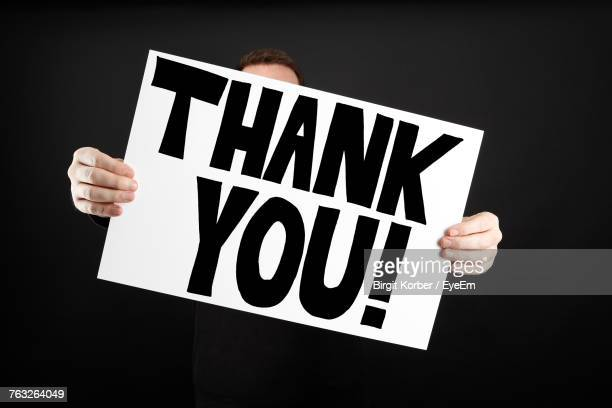 Man Holding Thank You Board While Standing Against Black Background