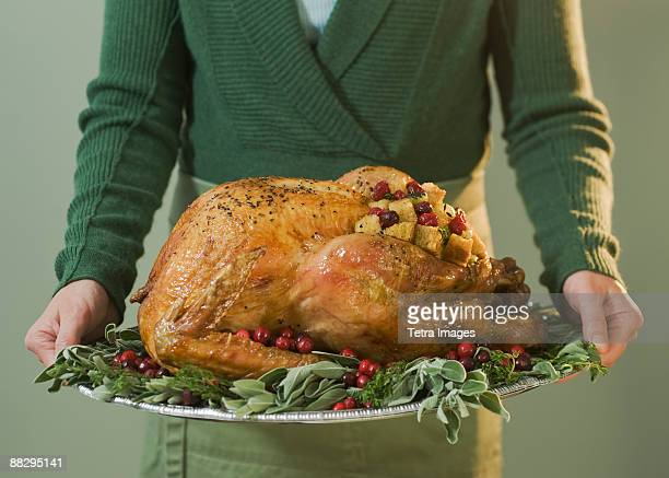 Man holding Thanksgiving turkey on decorated platter