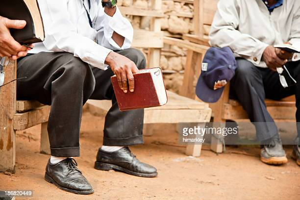 a man holding the bible and sitting on a park bench - christendom stockfoto's en -beelden