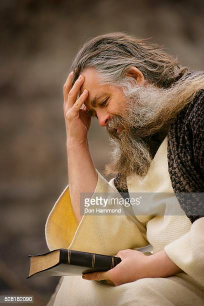 man holding the bible and thinking - historical reenactment stock photos and pictures