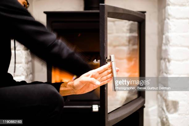 a man holding the door of the fireplace - cold temperature stock pictures, royalty-free photos & images