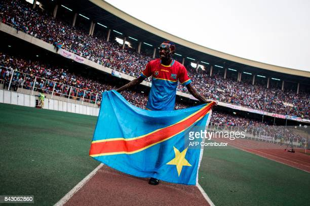 A man holding the flag of the Democratic Republic of the Congo national football team stands on the pitch prior to the FIFA World Cup 2018...