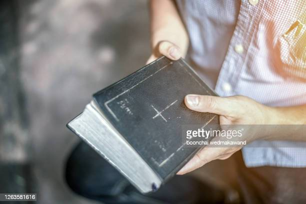 a man holding the holy bible. - pastor stock pictures, royalty-free photos & images