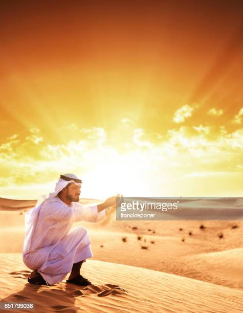 man holding the sand in the desert - united arab emirates flag stock photos and pictures
