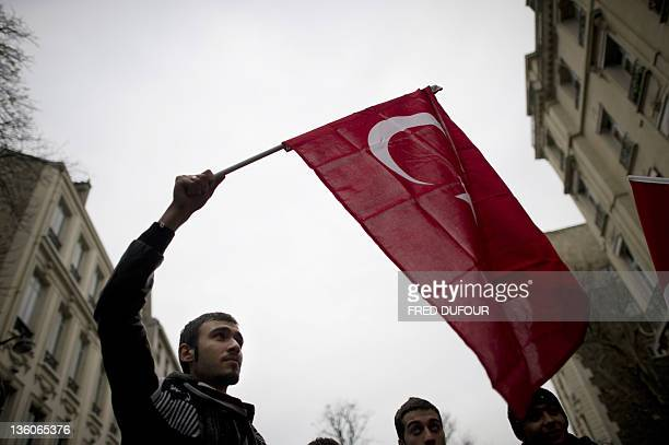 A man holding the Turkish flag takes part in a rally next to the French National Assembly on December 22 2011 in Paris as the French parliament is...