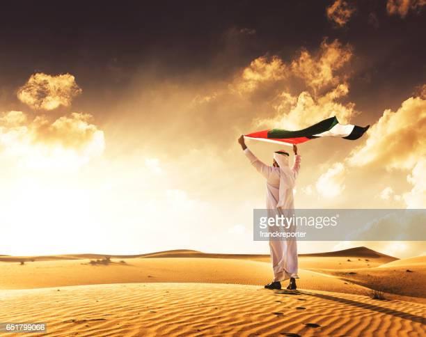 man holding the uae flag in the desert