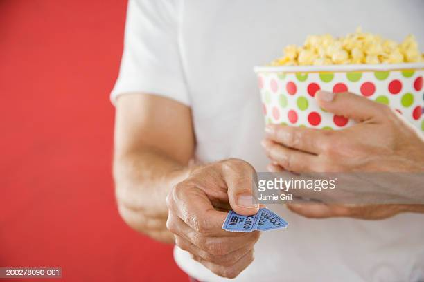 Man holding theatre tickets and box of popcorn, mid section