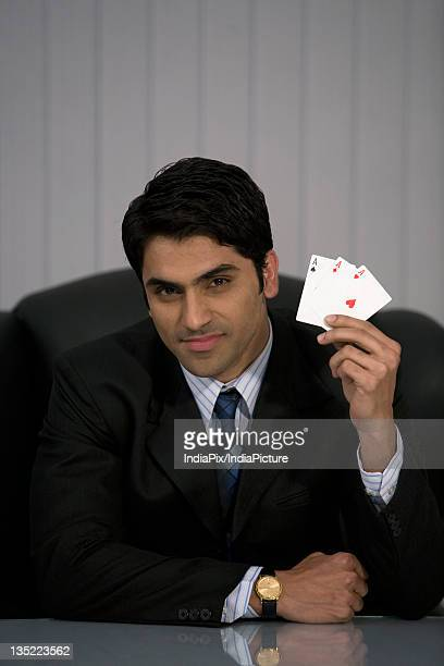 Man holding three aces
