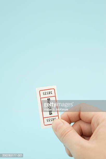 Man holding ticket with 'Success' written on it