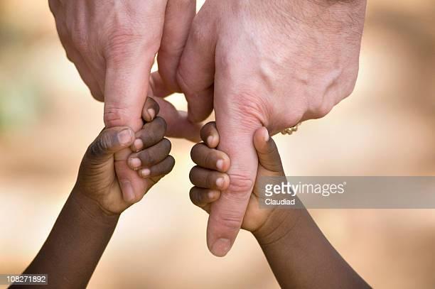 Homme tenant petites mains de l'enfant africain