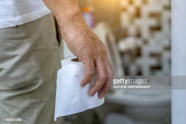 man holding toilet tissue roll in bathroom looking at loo - 下痢 ストックフォトと画像