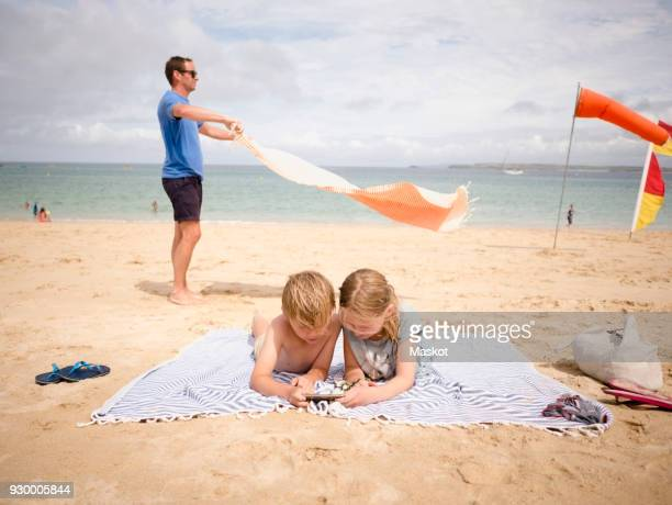 man holding towel while children sharing smart phone at beach against sky - little girl laying on the beach stock photos and pictures