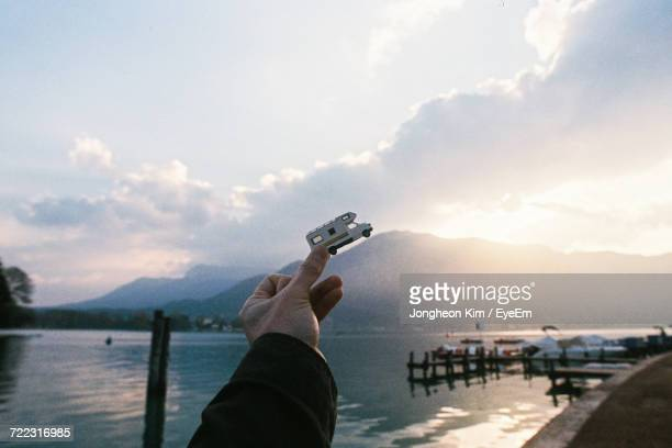 Man Holding Toy Car Against Sky