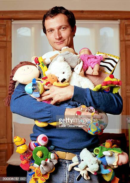 man holding toys in arms and stuffed into pockets, smiling, portrait - excess stock pictures, royalty-free photos & images