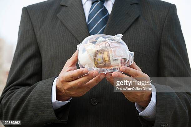Man holding transparent piggy bank filled with euros, cropped