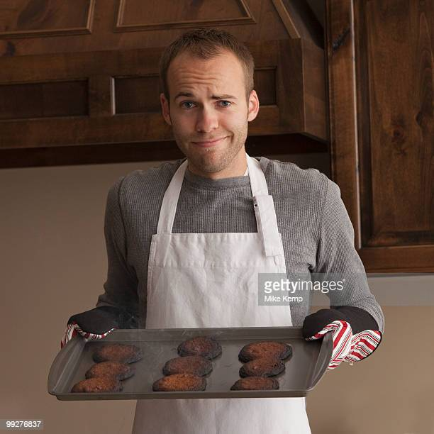Man holding tray of burnt cookies