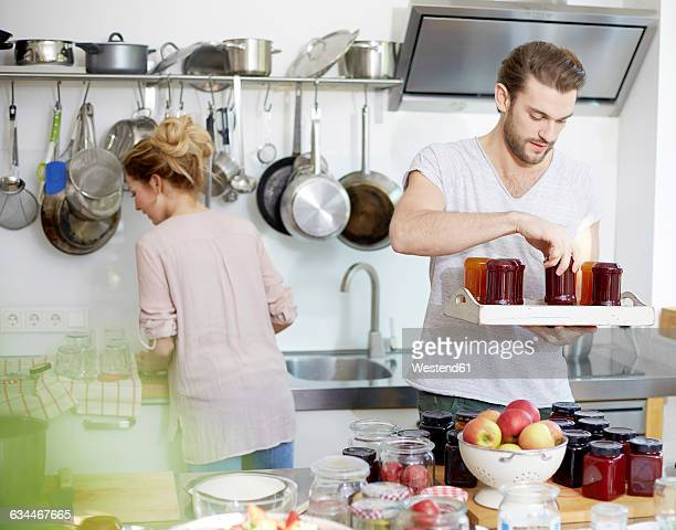 Man holding tray with jam jars in kitchen