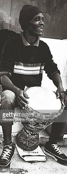Man Holding Tribal Drum Looking Away While Sitting On Seat