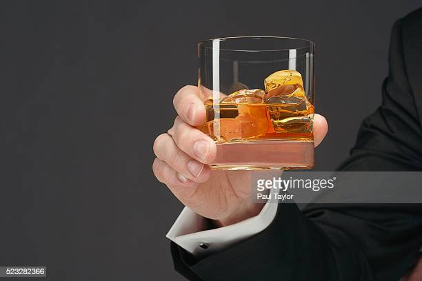 man holding tumbler of scotch - scotch whiskey stock pictures, royalty-free photos & images