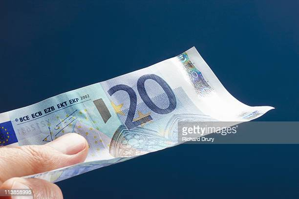 man holding twenty euro note - twenty euro banknote stock photos and pictures