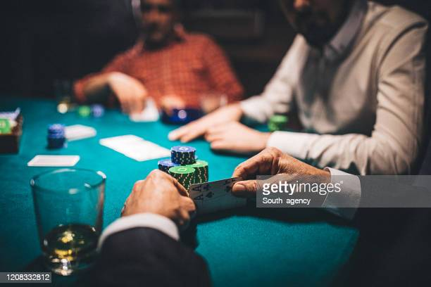 man holding two aces in poker game - gambling addiction stock pictures, royalty-free photos & images