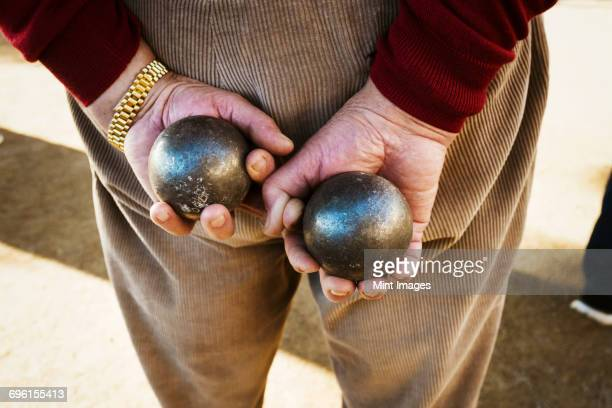 a man holding two boules, small metals balls in his hands behind his back. - ブール ストックフォトと画像