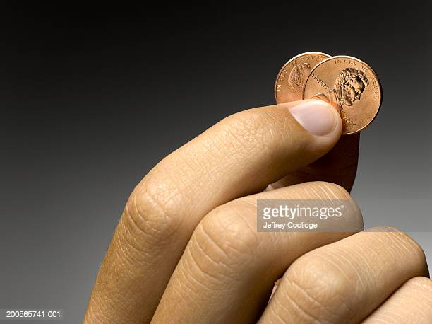 Man holding two pennies (focus on hand)