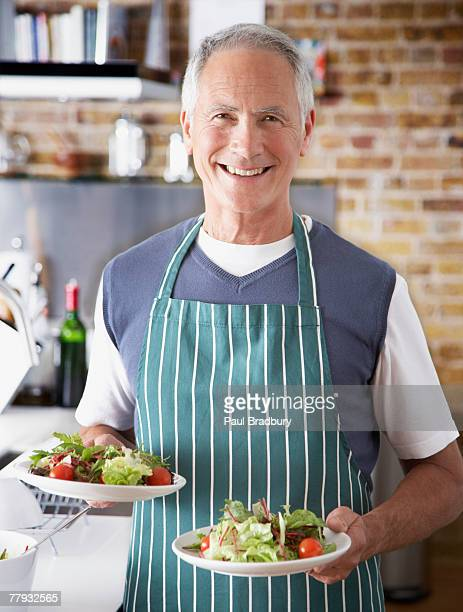 Man holding two plates of salad
