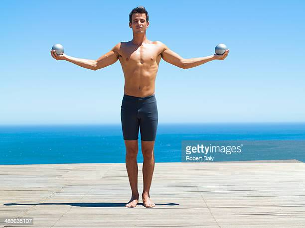 Man holding two small exercise balls with outstretched arms