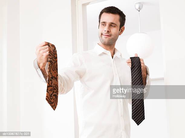 Man holding two ties
