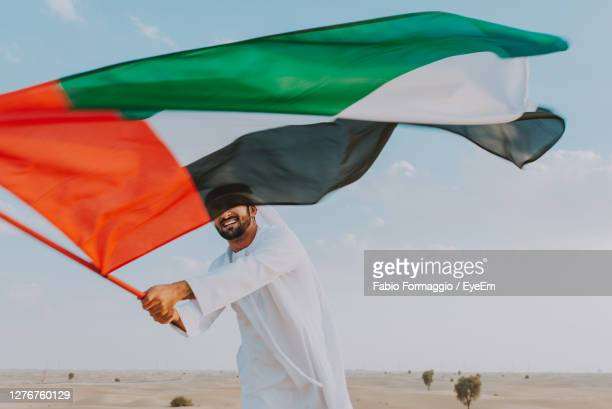 man holding umbrella on beach - middle east stock pictures, royalty-free photos & images
