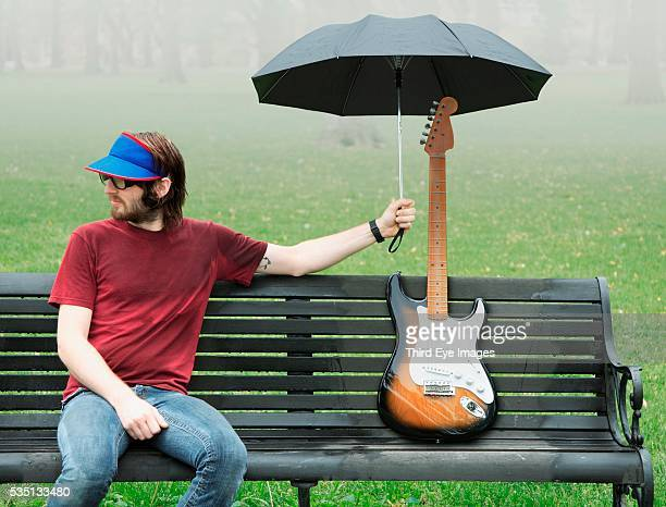 Man holding umbrella over electric guitar
