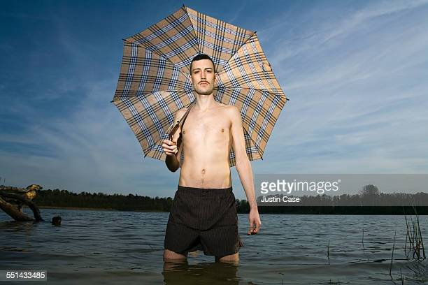 Man Holding Umbrella Standing In Water