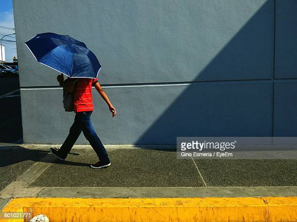 Man Holding Umbrella While Walking Against Wall On Sunny Day