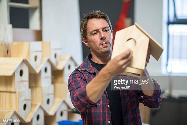 man holding unfinished birdhouse in workshop - birdhouse stock pictures, royalty-free photos & images