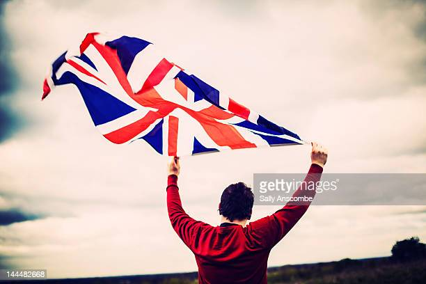 man holding union jack flag - union jack stock photos and pictures