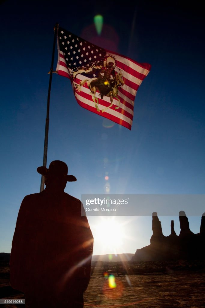 Man holding United States flag with Native American depiction near rock formations, Monument Valley, Utah, United States : Stock Photo