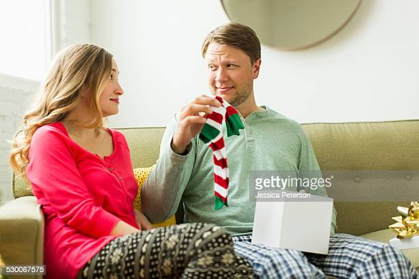 man holding unwanted christmas gift - negative emotion stock pictures, royalty-free photos & images