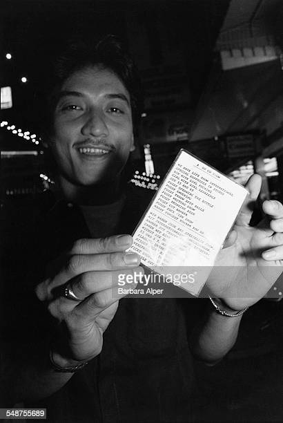 A man holding up a bilingual list in English and German of the various live sex acts on the bill at a gogo bar in Patpong a red light district of...